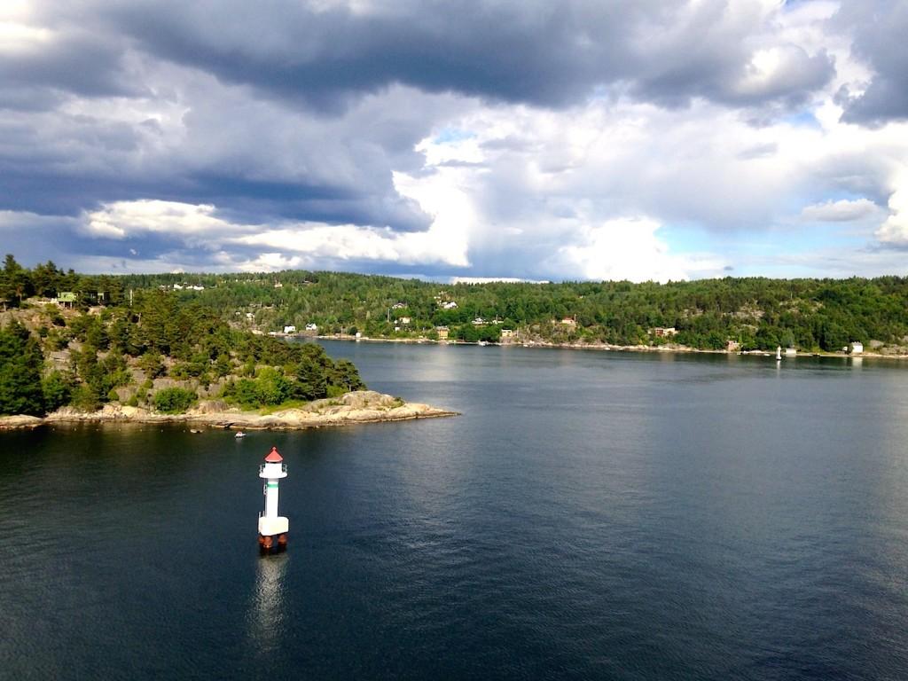 Har man familie eller kjentfolk langs fjorden er det obligatorisk å vinke når Københavnbåten seiler forbi. Litt vanskelig å se kanskje, men det står folk og vinker iherdig fra en av de gule hyttene på fastlandet. Har vi blitt fortalt i hvert fall.