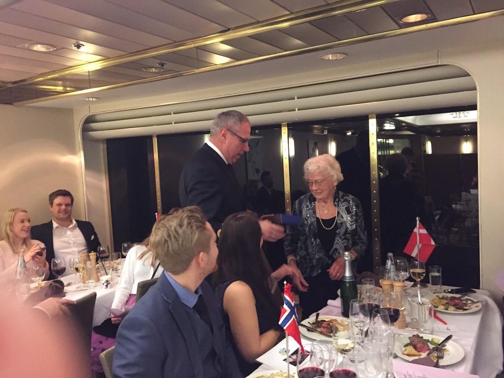 Kaptein Jens Knudsen overrasker og overreker en flaske champagne til jubilanten, som blir veldig glad.