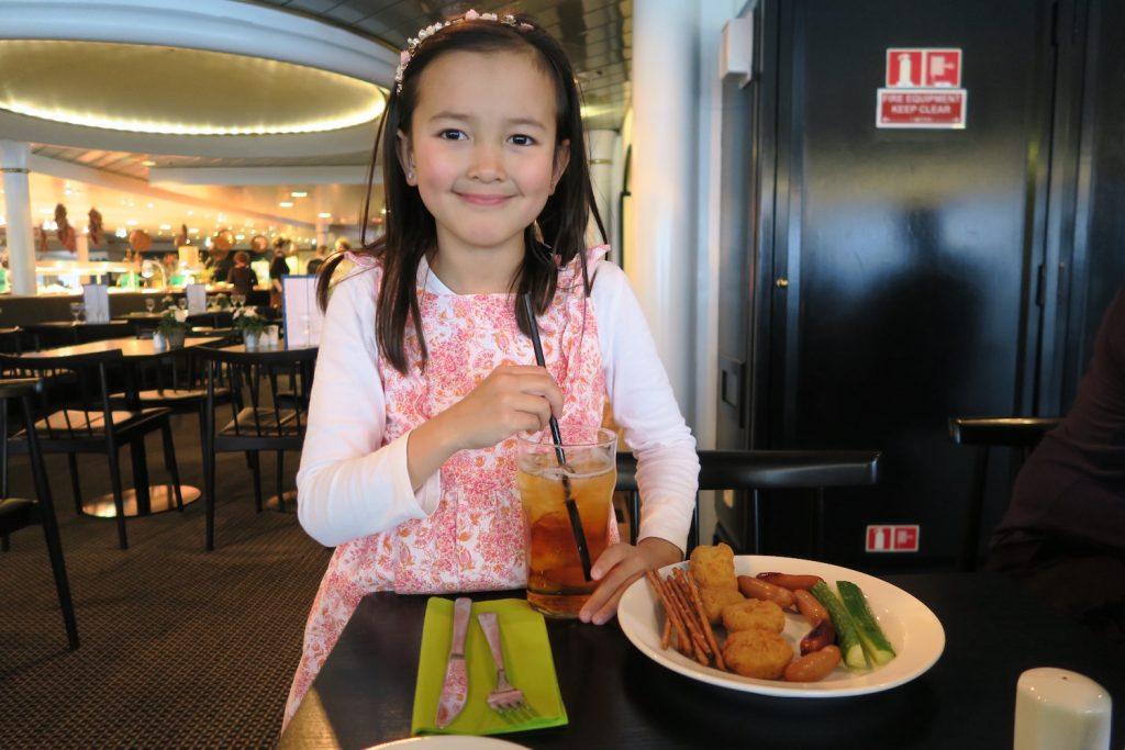 En superfornøyd jente gleder seg til å kose seg med middag om bord, med et stort glass eplejuice. Om bord på DFDS er alt så mye mer stas enn hjemme! Også maten!