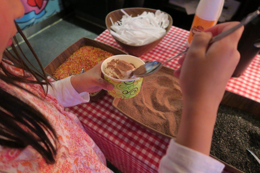 Etterpå kan man velge mellom ulike typer strø og sauser. Sjokoladepulver er favoritten. Iallfall i dag.